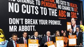 Ministers and Senators pose for media in front of a billboard showing an image of Prime Minister Tony Abbott at a ABC protest rally outside of Parliament House on 13 May 2014 in Canberra,
