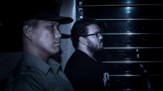 British banker Rurik Jutting (C), charged with the grisly murders of two women, sits in a prison van as he arrives at the eastern court in Hong Kong on November 24, 2014