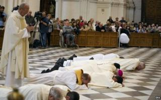 Granada's Archbishop, Francisco Javier Martinez, and other clerics prostrate themselves in front of Granada cathedral's high altar to ask forgiveness for alleged sexual abuses committed by priests on 23 November 2014.