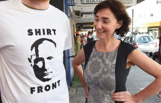 Fiona Stager (R) inspects a t-shirt her shop will give away for a donation featuring Russia's President Valdimar Putin and a quote from Australia's Prime Minister Tony Abbott threatening to 'shirt front' Putin - an Australian sporting term - when the two leaders meet at the G20 Leader's Summit in Brisbane on 13 November 2014.