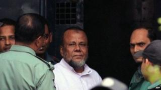 Bangladesh former ruling party official Mobarak Hossain (C) looks on as he enters a van at the International Crimes Tribunal court in Dhaka on November 24, 2014.