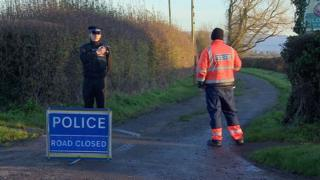 Policeman standing at end of private road