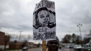 A protester displays a placard depicting 18-year-old Michael Brown on 24 November 2014