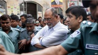 Bangladesh former minister Abdul Latif Siddique (C) is flanked by police officers at court after turning himself in in Dhaka