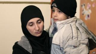 Nadia Abu Jamal holds her son at the home in East Jerusalem (26 November 2014)