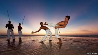 Capoeira dancers on a beach in Brazil