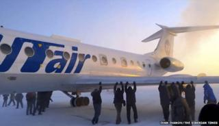 Passengers pushing plane