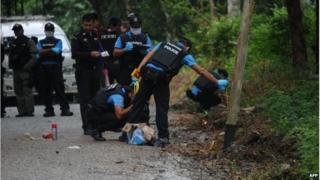 Thai police inspect the scene of a bomb blast in Narathiwat province (15 Nov 2014)
