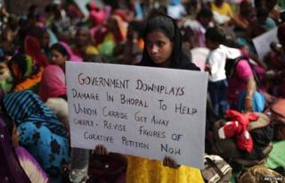 A child of a victim of the Bhopal gas tragedy, a gas leak from a Union Carbide pesticide plant that killed at least 3500 people, holds a placard during a sit-in protest in New Delhi November 10, 2014.