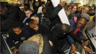 "Shoppers compete to purchase retail items on ""Black Friday"" at an Asda superstore in Wembley"