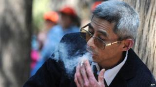 A man smokes a cigarette at a park in Beijing on May 11, 2010