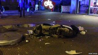 A scooter lies in pieces after a public toilet suddenly emerged from the ground