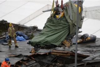 Rescuers lift the police helicopter wreckage from the roof of The Clutha pub