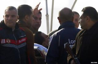 Policemen guard Hosni Mubarak on his stretcher as he is taken to a helicopter to fly to his trial in Cairo, 29 November