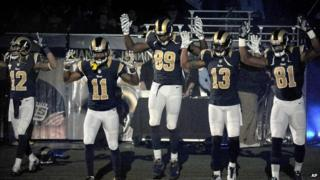 Five NFL players take the field in St Louis with a Ferguson protest gesture.