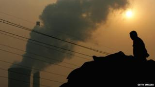 A Chinese man squats on a truck near a power plant emitting plumes of smoke from industrial chimneys on 30 October 2007 in Beijing, China.