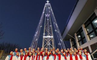 South Korean Christians sing a hymn in front of a Christmas tree atop a military-controlled hill near the tense land border in Gimpo, west of Seoul, on December 21, 2010