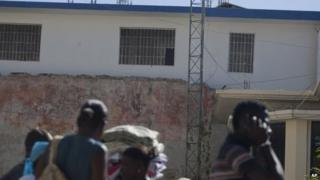 Residents walk by the Saint-Marc prison on 1 December, 2014.