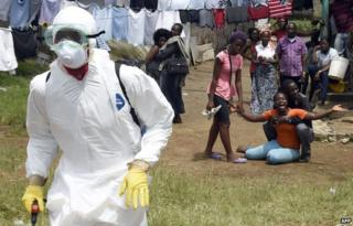 People look on at an Ebola worker in Monrovia, Liberia, on 4 October 2014