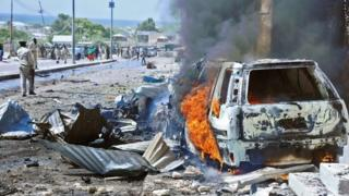 A car burns following a blast near the heavily fortified gates of the airport in Mogadishu on 3 December 2014