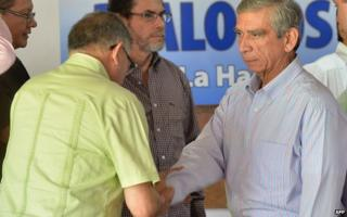 Farc delegate Rodrigo Granda (left) shakes hands with Jorge Enrique Mora (right), a member of the Colombian government's delegation, at Convention Palace in Havana on 3 December 2014.