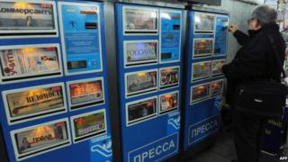 A man buying a newspaper from a self-service machine in Moscow