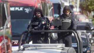 Mexican federal policemen patrol a street in Acapulco on 3 December, 2014.