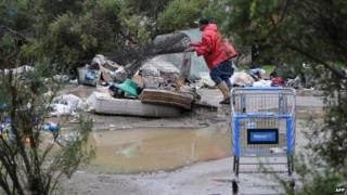 "An man pushes a trolley in a homeless encampment known as ""the Jungle"""