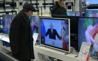 Customer watches President Putin in a TV shop in Moscow (4 Dec)