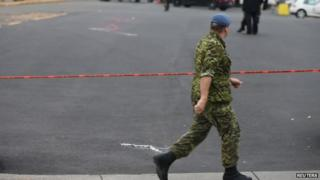 A member of Canada's armed forces walks past the scene of a hit and run of two soldiers in St. Jean sur Richelieu, Quebec, on 20 October 2014