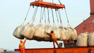 Workers unload goods from a ship at the port in Lianyungang, east China's Jiangsu province