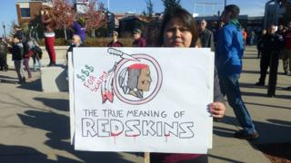 """A person at a protest in Minnesota holding up a sign criticising the use of the world """"redskin"""""""