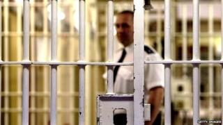 Prison officer seen through bars