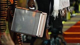 Big Brother Africa winner in 2003 holding up a suitcase with the prize money