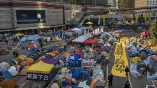 Protest banners block a main road along with tents set up by pro-democracy protesters outside the government headquarters at Admiralty in Hong Kong 8 December 2014