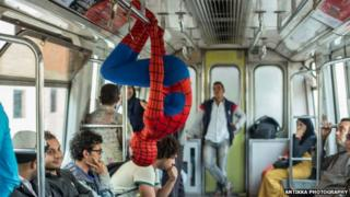 A man dressed as Spider-Man hangs upside down from a rail on the Cairo metro