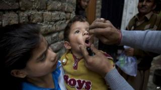 A Pakistani health worker gives a polio vaccine to a child in Islamabad, Pakistan, Monday, Dec. 8, 2014.