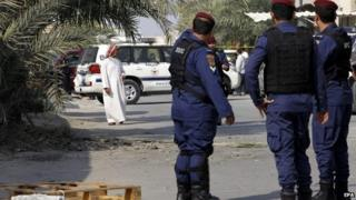 Police stand at the scene of the bombing in Karzakan, Bahrain (9 December 2014)