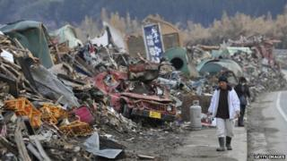 A couple walk through tsunami damage in Iwate in April 2011