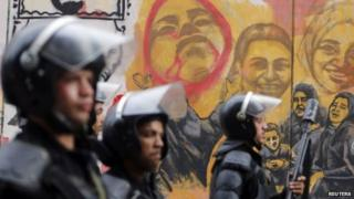 Riot police in front of a mural in Cairo's Tahrir Square remembering those killed in the 2011 uprising against Hosni Mubarak (19 November 2014)