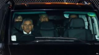 Shrien Dewani (back centre) is driven away from Gatwick Airport in a black people carrier
