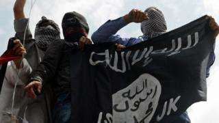 Kashmiri demonstrators hold up a flag of the Islamic State