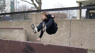 James performing a parkour jump over a metal barrier
