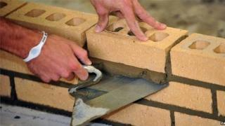 A construction worker laying bricks