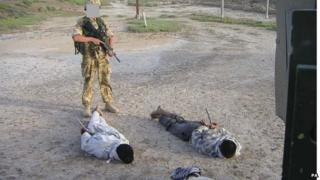 Detained Iraqis being guarded by a British soldier
