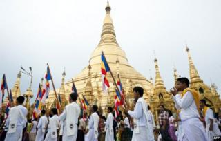 Buddhist devotees carry flags as they take part in a ceremony at the Shwedagon pagoda on the full moon day of Kasone Festival to mark Buddha's birthday in Yangon on 13 May 2014.
