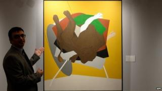 """Nishad Avari, Associate Specialist in South Asian Art, explains Tyeb Mehta""""s """"Untitled (Falling Bull)"""" during a media preview ahead of Christie""""s second auction in India, in Mumbai on December 9, 2014."""