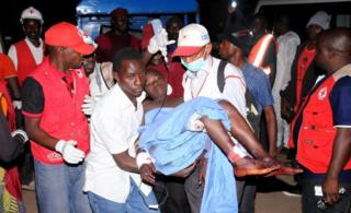 Rescue workers carry an injured victim of bomb blast on 11 December 2014 in Jos, Nigeria