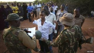 Passengers travelling to Nairobi wait to be searched for weapons in the town of Mandera at the Kenya-Somalia border, 8 December 2014