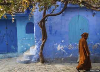 A man walks through the centre of Chefchaouen